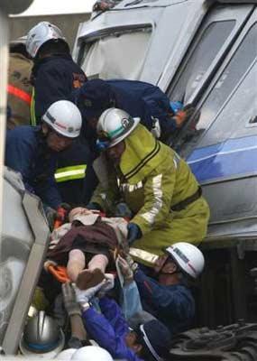 图文:日火车脱轨事故-救援人员正抬出受伤旅客