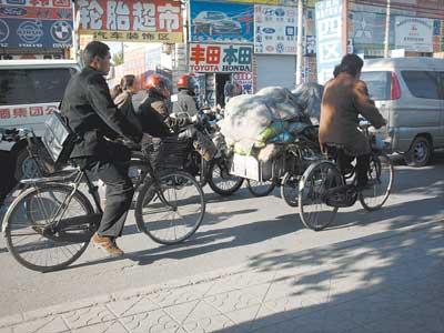 骑摩托车推三轮 危险!(图)