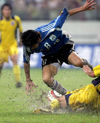 图文:中超四川0比4负大连 双方队员在雨中激战
