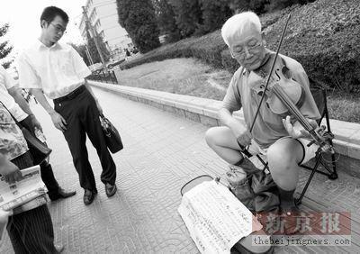 六旬老人街头拉琴卖艺 为女儿筹大学学费(图)