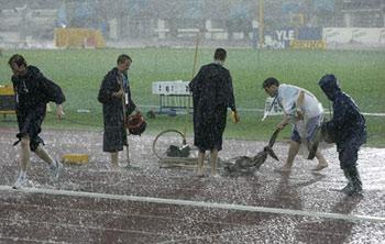 图文:田径世锦赛突降暴雨 工作人员在现场