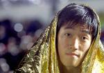 图文:刘翔晋级110米栏决赛 披着雨披一脸轻松