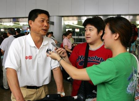 图文:中国田径队回国 冯树勇在机场接受采访