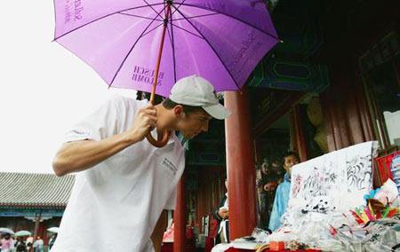 图文:菲尔普斯冒雨参观长城 对纪念品感兴趣