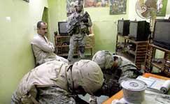 在伊拉克北部城市摩苏尔,一名伊拉克男子看着美国士兵搜查自己的商店。