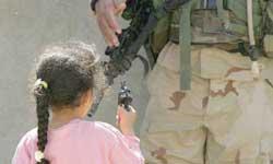 一个伊拉克女孩用塑料枪指着面前的美国士兵