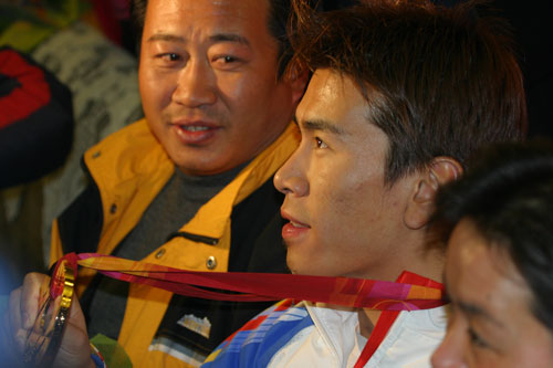 图文:冬奥会中国军团返回北京 韩晓鹏展示金牌