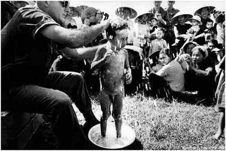 """正在给越南小孩洗澡,边上围着一圈儿""""看热闹的村民"""".-华裔记者图片"""