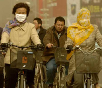 Local residents cycle against a sandstorm which hit Hohhot, North China's Inner Mongolia Autonomous Region Thursday March 9, 2006. Sandstorms frequent the northern part of China in the spring. [Xinhua]