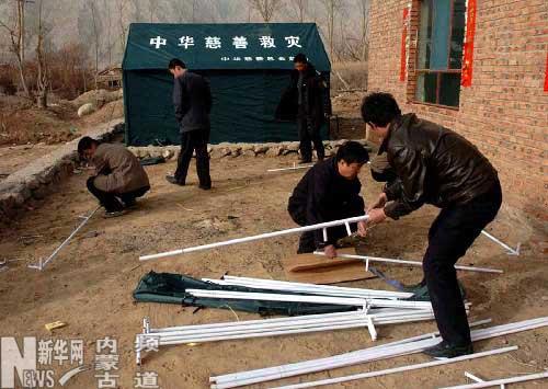 4月13日,在灾区内几名工作人员在搭建救灾帐篷.