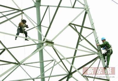 女子爬50米高压线铁塔 十名工人断电救人(组图)