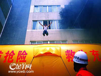 """学生从""""起火""""楼层跳到消防气垫逃生. 见习记者 郗慧晶/摄-300学图片"""