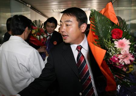 图文:国乒凯旋回国 刘国梁步出机舱后接受献花