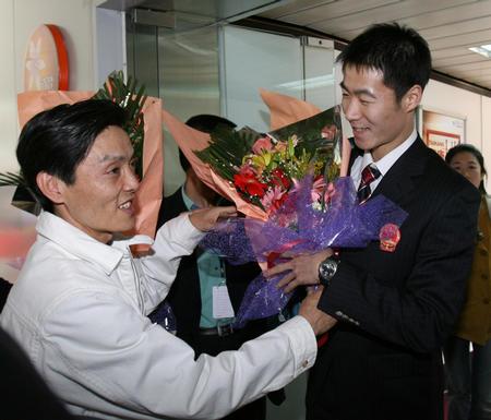 图文:国乒凯旋回国 王励勤接受陆元盛的献花