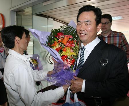 图文:国乒凯旋回国 蔡振华走出机舱接受献花