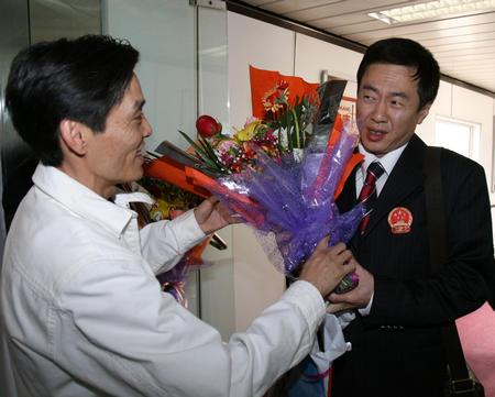 图文:国乒凯旋回国 施之皓接受陆元盛的献花
