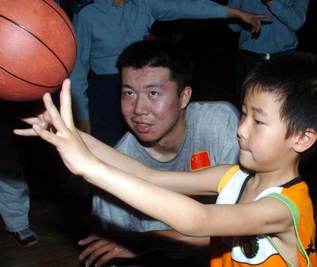 图文:国家男篮对抗赛 王治郅与小球迷玩游戏