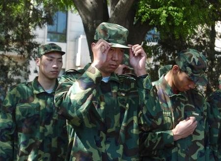 图文:国家男篮军训结束 王治郅表演前整理服装