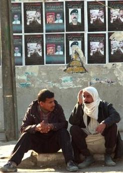 图文:伊拉克人坐在通缉扎卡维及支持者海报下
