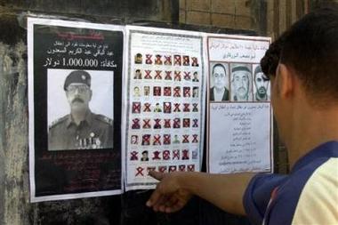 图文:一名伊拉克人正在看通缉悬赏海报