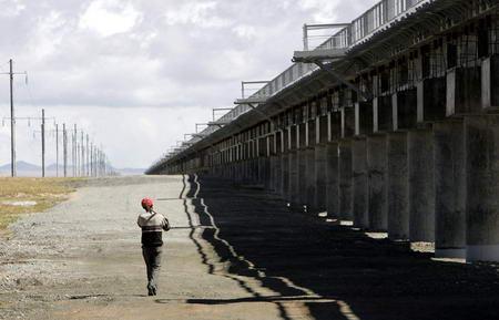 图文:一名工人从青藏铁路可可西里段附近走过