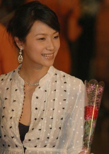 图:徐静蕾手拿玫瑰面带微笑 走过闭幕式红毯