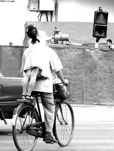 7月2日,一老者带着站在自行车后座的小女孩闯红灯过马路时,险些被