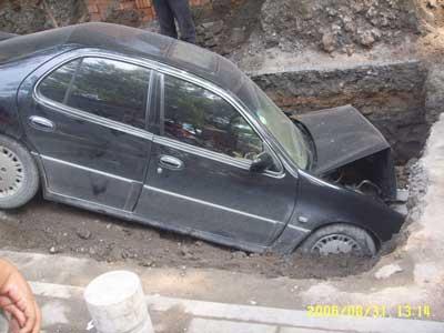 掉入大坑的尼桑轿车车头已变形.高清图片