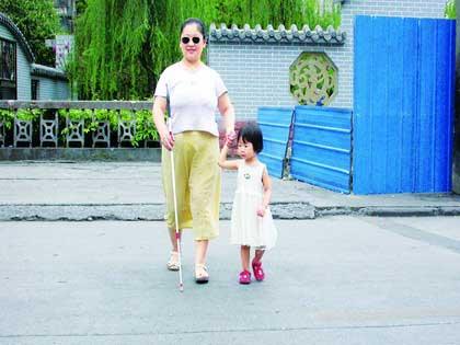 扶盲人过马路的图片-失明女子没钱供女儿上学 天天带其模拟上学