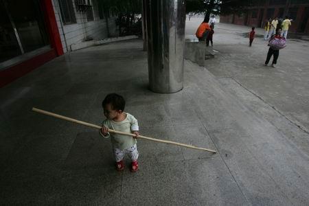 武校 暑假 少林/一个刚满1岁的小女孩拿着木棍在玩,她跟着妈妈前来探视学武的...