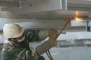 图文:鸟巢实施钢结构卸载 现场工人进行焊接