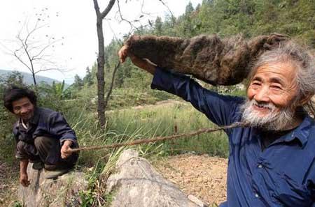 老人与儿子展示他得意的长发和胡须.图片