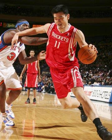 NBA图:火箭客场胜尼克斯 姚明带球突破库里防守
