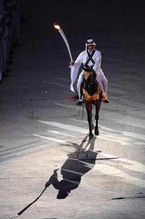 图文:多哈亚运会开幕式点火仪式 骑士手持火炬