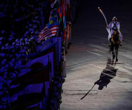 图文:亚运会开幕式点火仪式 骑士手持火炬绕场