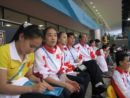 图文:体操男团中国夺冠 女队员认真观战做记录