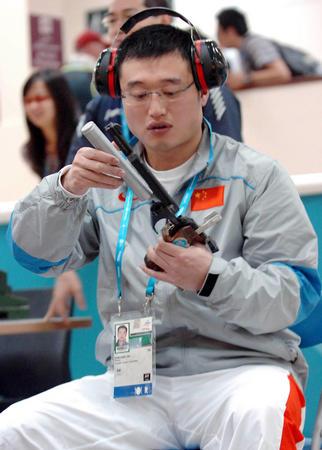 图文:男10米气手枪团体赛 谭宗亮赛后整理枪械