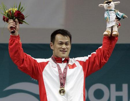 图文:男子举重69公斤级张国政夺金 在领奖台上