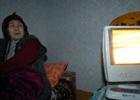 一名妇女用电暖器取暖