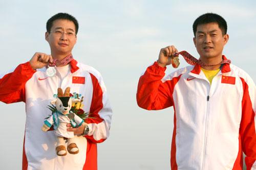 图文:男子25米手枪速射团体赛 队员夺冠后微笑