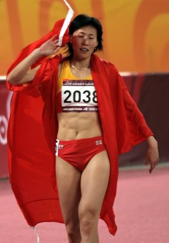 独家图片:夺得400米栏冠军 黄潇潇身披国旗绕场