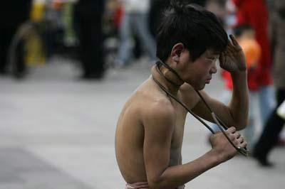 少年街头卖艺 钢丝勒脖自虐表演震惊路人(组图)