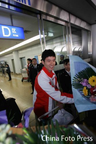 图文:中国亚运羽球健儿返回抵京 蔡赟笑容满面