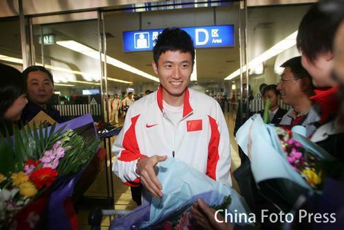 图文:中国亚运羽球健儿返回北京 蔡赟接受鲜花