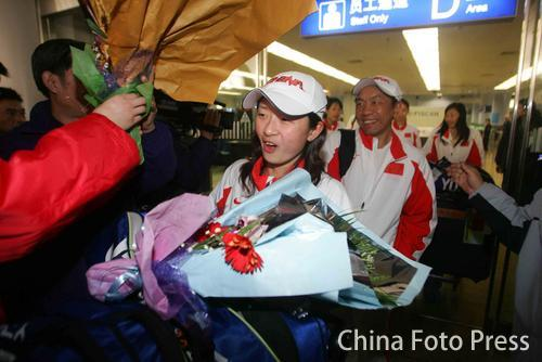 图文:中国亚运羽球健儿返京 张亚雯手捧鲜花