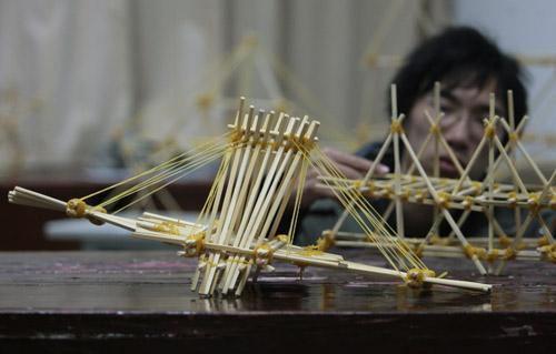 筷子桥梁论+�yf_一名学生正在观看用筷子和皮筋搭建而成的\