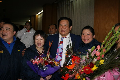 图文:中国亚运代表团抵京 手捧鲜花合影