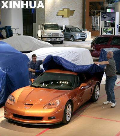 1月2日,工人在美国密歇根州底特律为将在北美国际汽车展上展出的汽车蒙上防尘罩。北美国际汽车展将在1月13日开幕。 新华社/法新
