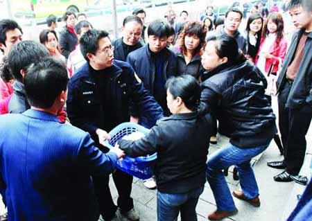 黄兴南路上,城管队员在没收流动摊贩所摆卖的物品。