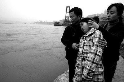 佳佳(中)在孙芳的陪同下思念着被江水卷走的父亲 记者欧阳祖兵摄